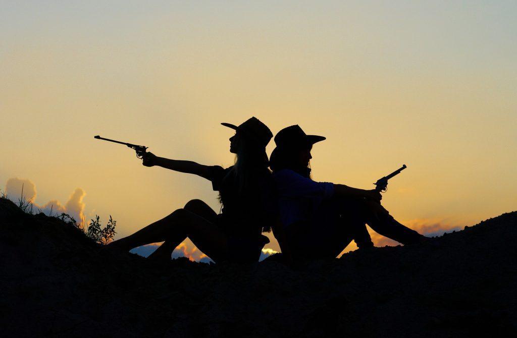 sylwetki dwóch osób siedzących z rewolwerami w dłoniach